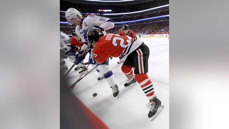 Tampa Bay Lightning center Steven Stamkos (91) and Chicago Blackhawks defenseman Johnny Oduya (27) vies for a loose puck along the boards, during the first period of an NHL hockey game Tuesday, Nov. 11, 2014, in Chicago. (AP Photo/Charles Rex Arbogast)