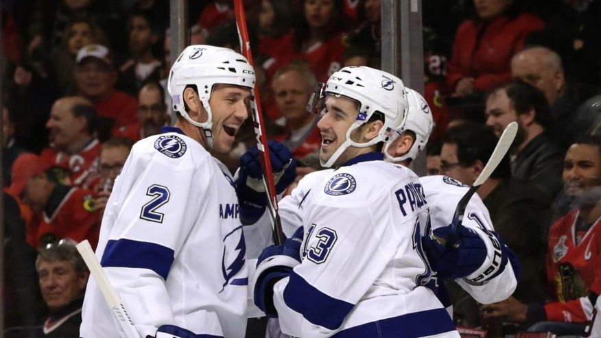 Tampa Bay Lightning center Cedric Paquette (13) celebrates with Eric Brewer (2) and Ondrej Palat after Paquette's goal on Chicago Blackhawks goalie Corey Crawford during the first period of an NHL hockey game Tuesday, Nov. 11, 2014, in Chicago. (AP Photo/Charles Rex Arbogast)