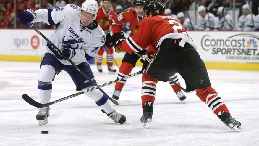 Tampa Bay Lightning left wing Ondrej Palat (18) advances the puck into the Blackhawks' zone past defenseman Duncan Keith (2), during the first period of an NHL hockey game Tuesday, Nov. 11, 2014, in Chicago. (AP Photo/Charles Rex Arbogast)