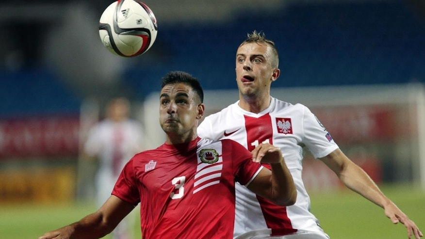 """FILE - This is a Sunday Sept. 7, 2014 file photo of Gibraltar's Joseph Chipolina, left, as he  tussles for the ball with Poland's Kamil Grosicki during an Euro 2016 Group D qualifying round soccer match between Gibraltar and Poland at the Algarve stadium in Faro, southern Portugal, Sunday, Sept. 7, 2014.  Days before one of world football's biggest ever mismatches, the captain of Gibraltar laughs as he contemplates the task facing his team of amateurs against Germany.""""To put things in perspective, we have gone from Sunday league football to playing the world champions in 18 months,"""" Roy Chipolina said, shaking his head in bewilderment. """"Sometimes I have to pinch myself."""" (AP Photo/Francisco Seco, File)"""