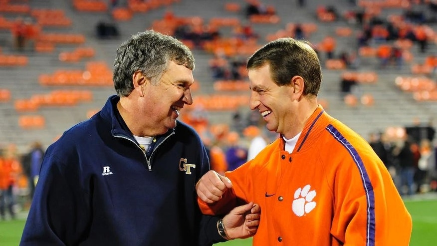 FILE - In this Nov. 14, 2013, file photo, Georgia Tech head coach Paul Johnson, left, laughs with Clemson coach Dabo Swinney before an NCAA college football game in Clemson, S.C. No. 24 Georgia Tech's running attack, which ranks second in the nation, will be tested by No. 18 Clemson's defense, which ranks second overall and No. 4 against the run, on Saturday, Nov. 15, 2014, in Atlanta.  (AP Photo/ Richard Shiro, File)