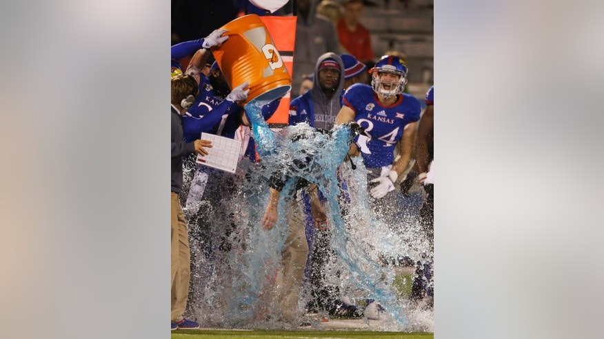 Kansas head coach Clint Bowen gets doused during the second half of an NCAA college football game against Iowa State in Lawrence, Kan., Saturday, Nov. 8, 2014. Kansas defeated Iowa State 34-14. It was his first win as a head coach. (AP Photo/Orlin Wagner)