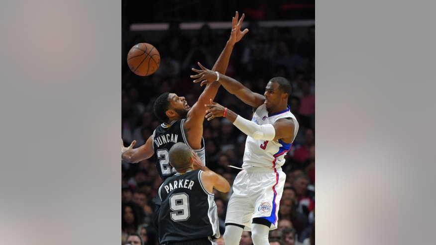 Los Angeles Clippers guard Chris Paul, right, passes the ball by San Antonio Spurs forward Tim Duncan, left, as guard Tony Parker, of France, looks on during the first half of an NBA basketball game, Monday, Nov. 10, 2014, in Los Angeles. (AP Photo/Mark J. Terrill)