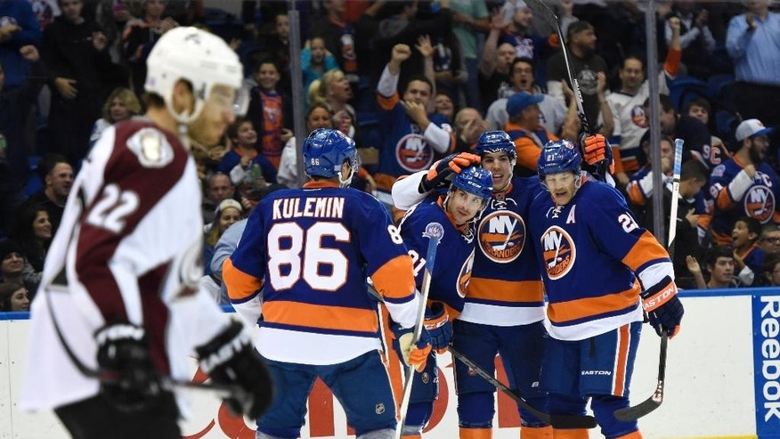 New York Islanders defenseman Travis Hamonic (3) celebrates his goal with  center John Tavares (91), Kyle Okposo (21) and left wing Nikolai Kulemin (86) as Colorado Avalanche defenseman Zach Redmond (22) reacts in the second period of an NHL hockey game at Nassau Coliseum on Tuesday, Nov. 11, 2014, in Uniondale, N.Y. (AP Photo/Kathy Kmonicek)
