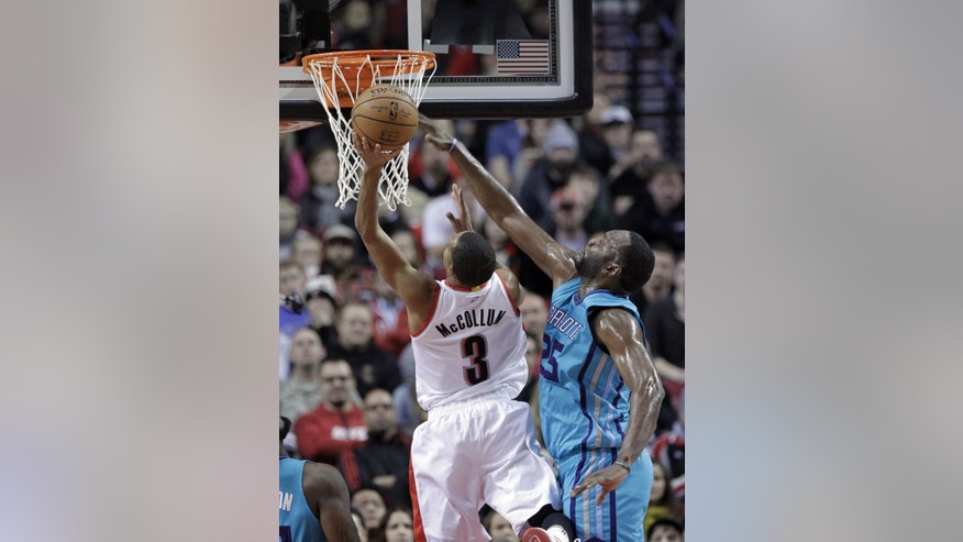 Charlotte Hornets center Al Jefferson, right, blocks a shot by Portland Trail Blazers guard CJ McCollum during the first half of an NBA basketball game in Portland, Ore., Tuesday, Nov. 11, 2014.(AP Photo/Don Ryan)