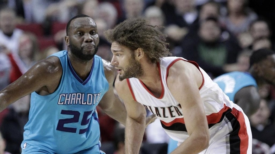 Portland Trail Blazers center Robin Lopez, right, drives on Charlotte Hornets center Al Jefferson during the first half of an NBA basketball game in Portland, Ore., Tuesday, Nov. 11, 2014.(AP Photo/Don Ryan)