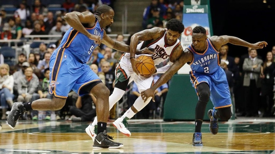 Milwaukee Bucks' O.J. Mayo vies for a loose ball with Oklahoma City Thunder's Kendrick Perkins and Anthony Morrow (2) during the second half of an NBA basketball game Tuesday, Nov. 11, 2014, in Milwaukee. (AP Photo/Morry Gash)