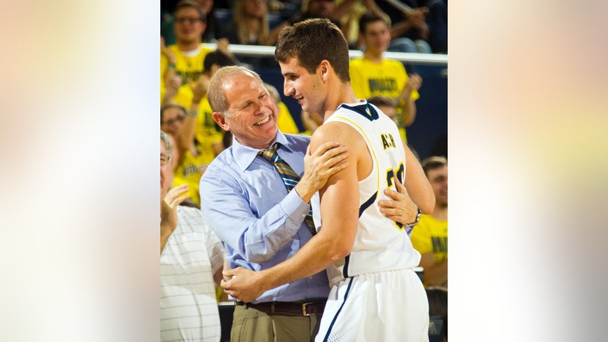 Michigan head coach John Beilein congratulates guard Austin Hatch after he made a free throw basket in the second half of an NCAA college basketball exhibition game against Wayne State at Crisler Center in Ann Arbor, Mich., Monday, Nov. 10, 2014. Michigan won 86-43. Hatch is a two-time airplane crash survivor who lost all of his immediate family members. (AP Photo/Tony Ding)