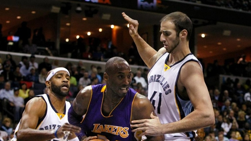 Los Angeles Lakers Kobe Bryant goes betwen Mphis Grizzlies Kosts Koufos (41) and Vince Carter (15) in the first half of an NBA basketball game Tuesday, Nov. 11, 2014, in Memphis, Tenn. (AP Photo/Karen Pulfer Focht)