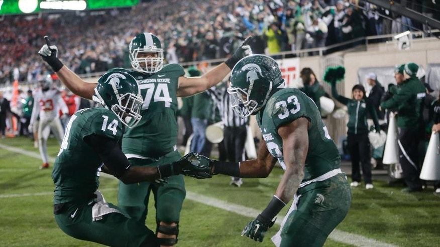 Michigan State running back Jeremy Langford (33) celebrates with wide receiver Tony Lippett (14) and offensive tackle Jack Conklin (74) after his a 33-yard touchdown run against Ohio State during the first half of an NCAA college football game in East Lansing, Mich., Saturday, Nov. 8, 2014. (AP Photo/Carlos Osorio)
