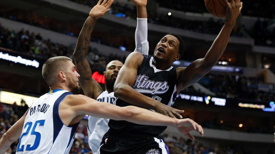 Sacramento Kings forward Rudy Gay (8) fights for a shot opportunity against Dallas Mavericks' Chandler Parsons (25) and Tyson Chandler, rear, in the first half of an NBA basketball game, Tuesday, Nov. 11, 2014, in Dallas. (AP Photo/Tony Gutierrez)