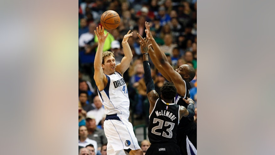Dallas Mavericks' Dirk Nowitzki (41) of Germany is forced to pass the ball under pressure from Sacramento Kings' Ben McLemore (23) and Carl Landry, right rear, in the first half of an NBA basketball game, Tuesday, Nov. 11, 2014, in Dallas. (AP Photo/Tony Gutierrez)