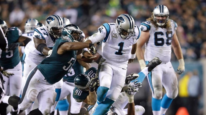 Carolina Panthers' Cam Newton (1) fumbles the ball as he is brought down by Philadelphia Eagles' Connor Barwin (98) and Brandon Graham (55) during the second half of an NFL football game, Monday, Nov. 10, 2014, in Philadelphia. (AP Photo/Michael Perez)