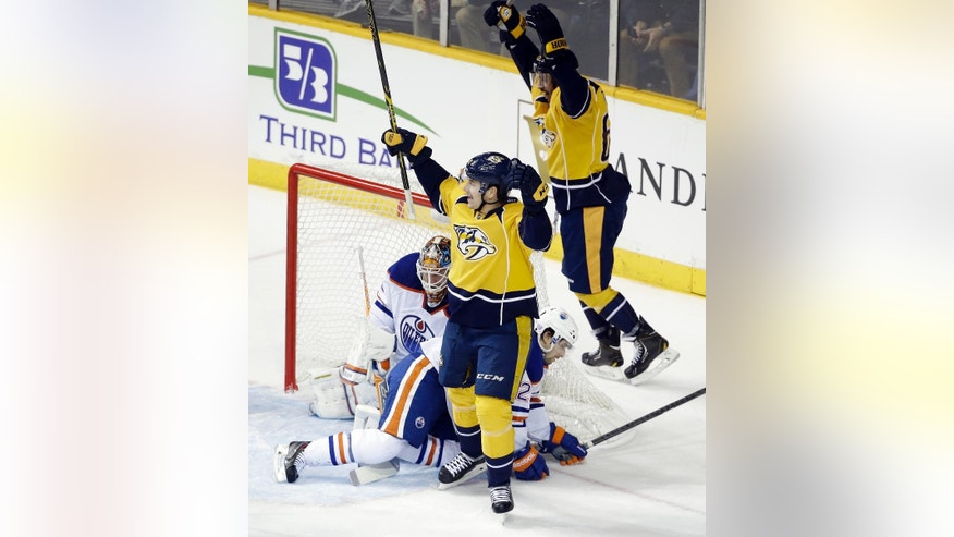 Nashville Predators' Filip Forsberg, center, of Sweden, celebrates after scoring against Edmonton Oilers goalie Viktor Fasth, of Sweden, in the first period of an NHL hockey game Tuesday, Nov. 11, 2014, in Nashville, Tenn. Also defending for Edmonton is Mark Arcobello (26). (AP Photo/Mark Humphrey)