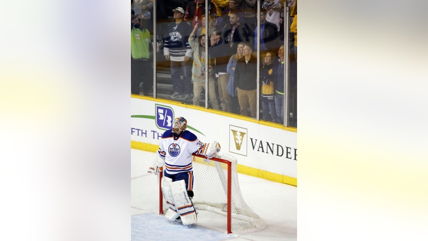 Edmonton Oilers goalie Viktor Fasth, of Sweden, watches the replay on the scoreboard after giving up a goal to Nashville Predators' Filip Forsberg in the first period of an NHL hockey game Tuesday, Nov. 11, 2014, in Nashville, Tenn. (AP Photo/Mark Humphrey)