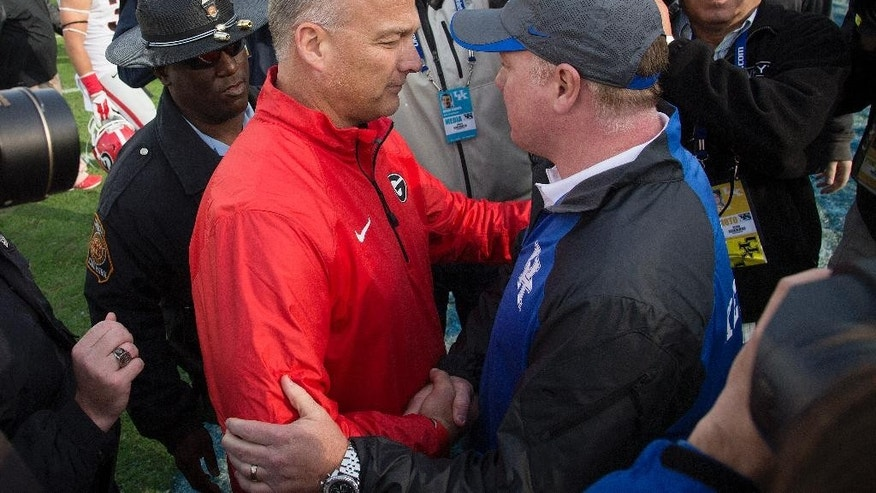 Georgia head coach Mark Richt, left, is congratulated by Kentucky head coach Mark Stoops midfield after their NCAA college football game at Commonwealth Stadium in Lexington, Ky., Saturday, Nov. 8, 2014. Georgia beat Kentucky 63-31. (AP Photo/David Stephenson)