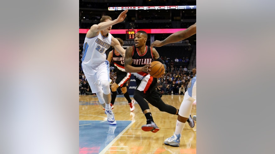 Portland Trail Blazers guard Damian Lillard drives past Denver Nuggets center Timofey Mozgov (25) during the first half of an NBA basketball game Wednesday, Nov. 12, 2014, in Denver. (AP Photo/Jack Dempsey)
