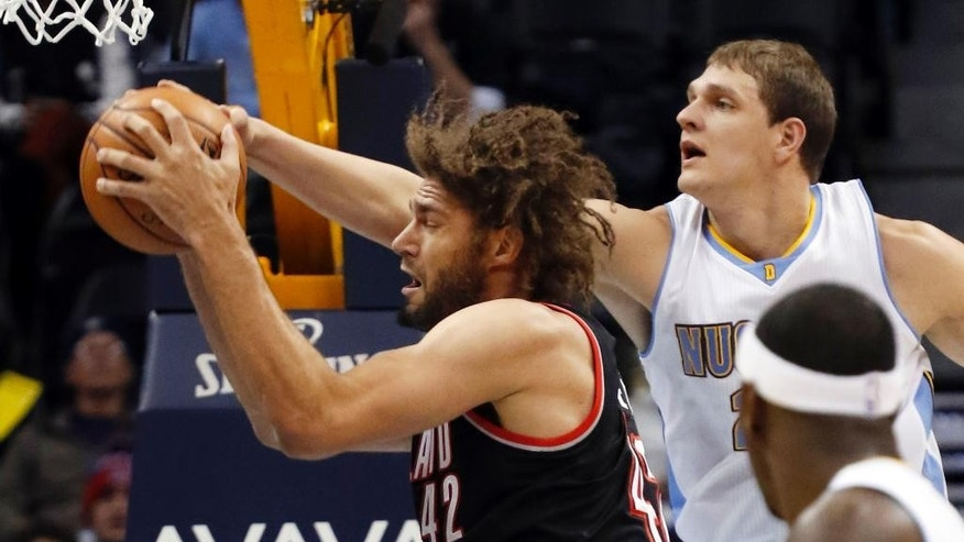 Denver Nuggets center Timofey Mozgov (25) gets a hand on the ball as Portland Trail Blazers center Robin Lopez (42) grabs a rebound during the first half of an NBA basketball game Wednesday, Nov. 12, 2014, in Denver. (AP Photo/Jack Dempsey)
