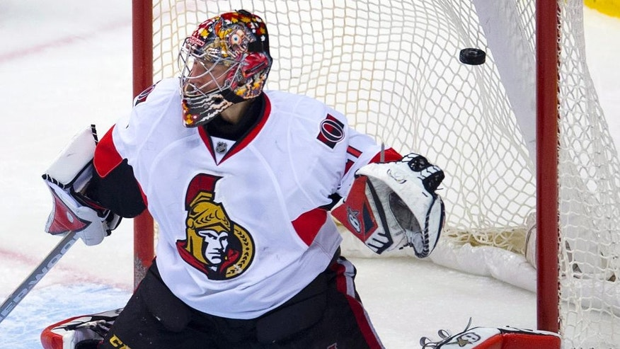 Vancouver Canucks left wing Daniel Sedin's goal goes past Ottawa Senators goalie Craig Anderson during overtime in an NHL hockey game Tuesday, Nov. 11, 2014, in Vancouver, British Columbia. Vancouver won 4-3. (AP Photo/The Canadian Press, Jonathan Hayward)