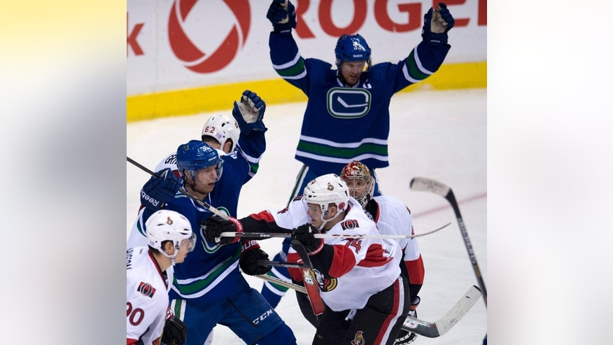 Vancouver Canucks' Jannik Hansen (36) and Henrik Sedin (33) celebrate teammate Kevin Bieksa's goal against the Ottawa Senators during the third period of an NHL hockey game Tuesday, Nov. 11, 2014, in Vancouver, British Columbia. (AP Photo/The Canadian Press, Jonathan Hayward)