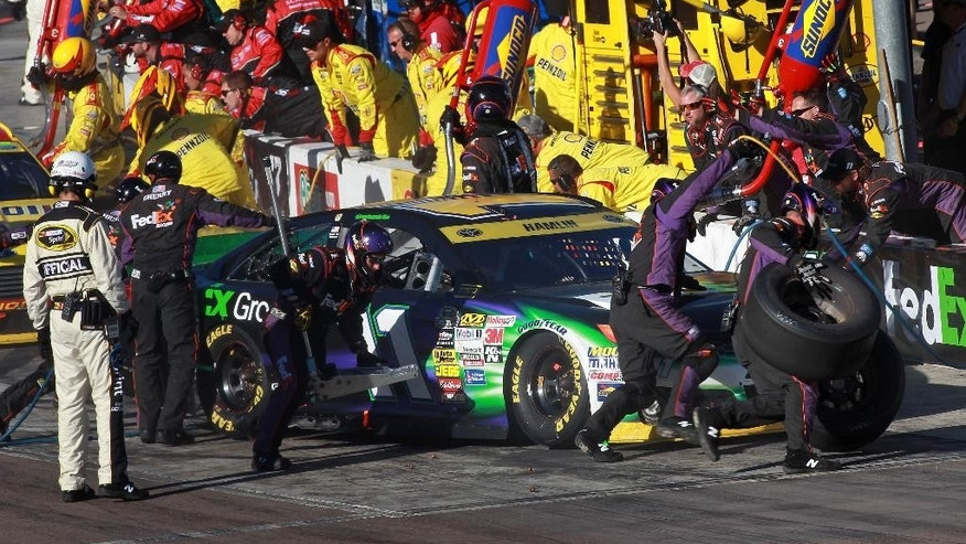 Crew members for driver Denny Hamlin go to work on his car during a pit stop in the Quicken Loans Race for Heroes 500 NASCAR Sprint Cup Series auto race at Phoenix International Raceway, Sunday, Nov. 9, 2014 in Avondale, Ariz. (AP Photo/Ralph Freso)