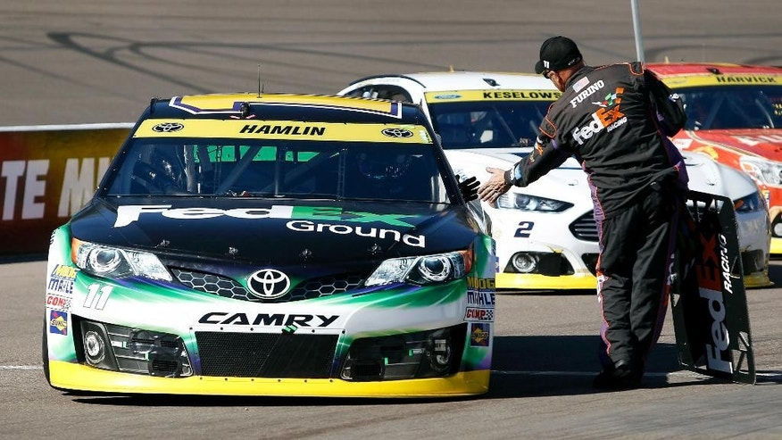 A pit crew member shakes driver Denny Hamlin's hand as he exits the pit area during the start of the Quicken Loans Race for Heroes 500 NASCAR Sprint Cup Series auto race at Phoenix International Raceway, Sunday, Nov. 9, 2014 in Avondale, Ariz. Hamlin was the pole winner for the race. (AP Photo/Ralph Freso)