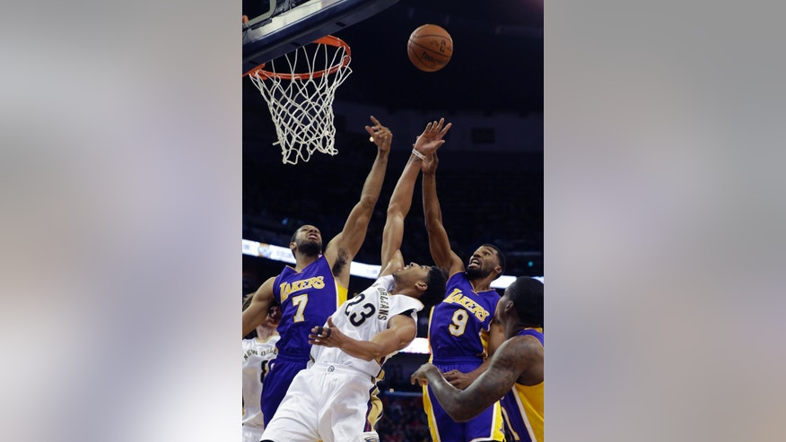 New Orleans Pelicans forward Darius Miller (23) reaches for a rebound against Los Angeles Lakers forward Xavier Henry (7) and guard Ronnie Price (9) during the first half of an NBA basketball game in New Orleans, Wednesday, Nov. 12, 2014. (AP Photo/Gerald Herbert)