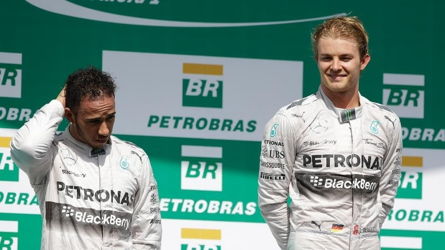 Mercedes driver Nico Rosberg of Germany, right, and teammate Lewis Hamilton of Britain, stand on the podium for Formula One Brazilian Grand Prix at the Interlagos race track in Sao Paulo, Brazil, Sunday, Nov. 9, 2014. Rosberg fended off a strong charge by Hamilton to win the Brazilian Grand Prix on Sunday, closing in on his Mercedes teammate in the Formula One title race. (AP Photo/Ricardo Mazalan)