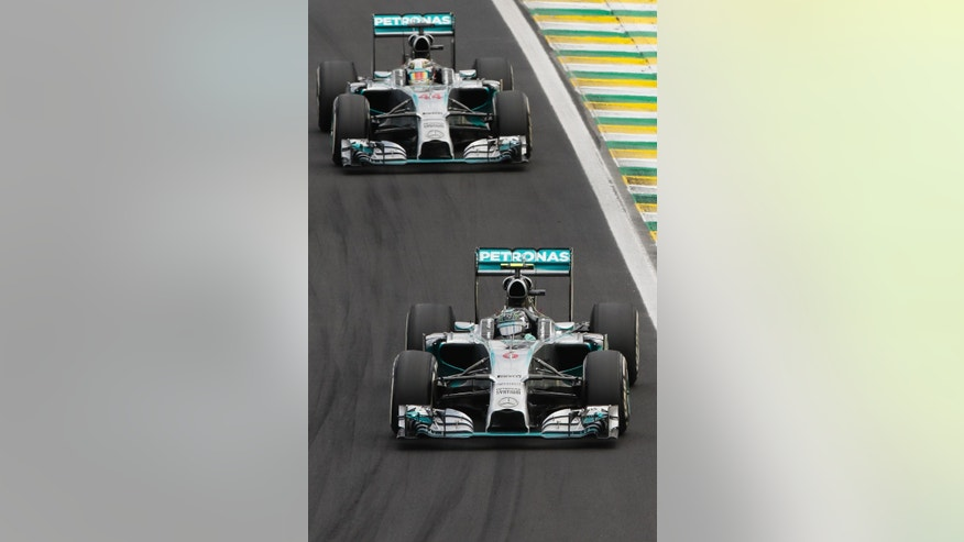 Mercedes driver Nico Rosberg of Germany, steers his car ahead of teammate Lewis Hamilton of Britain, during the Formula One Brazilian Grand Prix at the Interlagos race track in Sao Paulo, Brazil, Sunday, Nov. 9, 2014. Rosberg fended off a strong charge by Hamilton to win the Brazilian Grand Prix on Sunday, closing in on his Mercedes teammate in the Formula One title race. (AP Photo/Andre Penner)