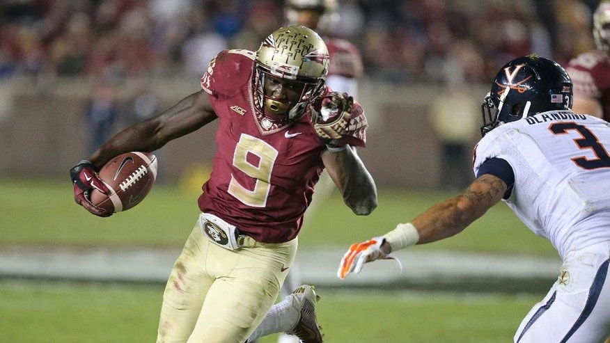 Florida State's Karlos Williams picks up yardage as Virginia's Quin Blanding moves in for the tackle in the fourth quarter of their NCAA college football game, Saturday, Nov. 8, 2014, in Tallahassee, Fla. Florida State won the game 34-20. (AP Photo/Steve Cannon)