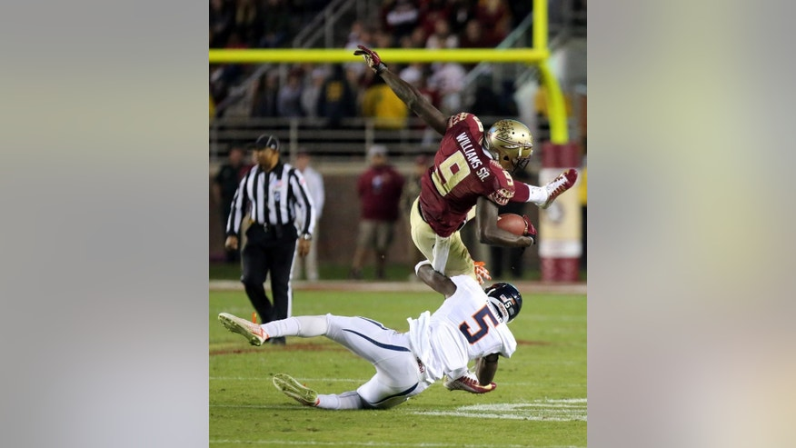 Virginia's Tim Harris (5) upends Florida State's Karlos Williams on a run play in the third quarter of an NCAA college football game, Saturday, Nov. 8, 2014, in Tallahassee, Fla. Florida State won the game 34-20. (AP Photo/Steve Cannon)
