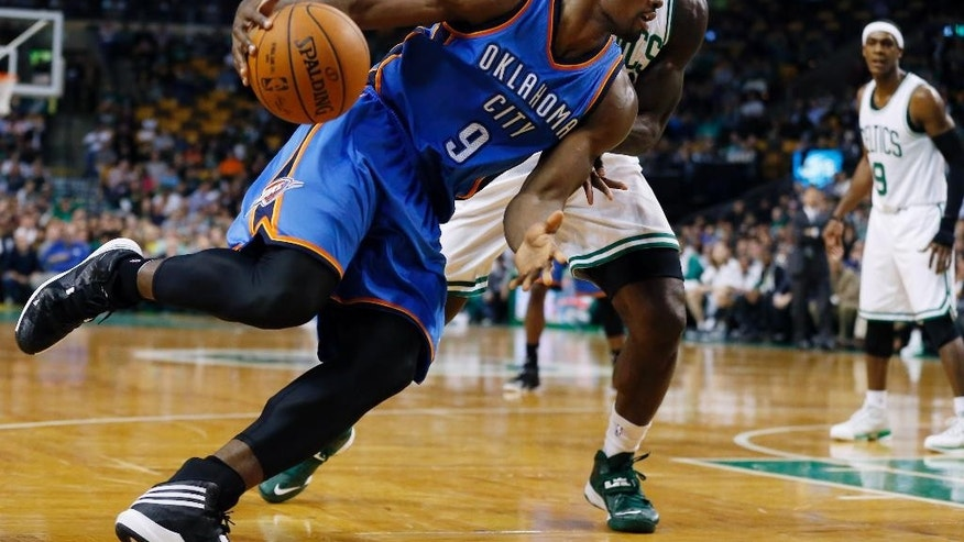 Oklahoma City Thunder forward Serge Ibaka (9) drives against Boston Celtics forward Brandon Bass during the first half of an NBA basketball game in Boston, Wednesday, Nov. 12, 2014. (AP Photo/Elise Amendola)