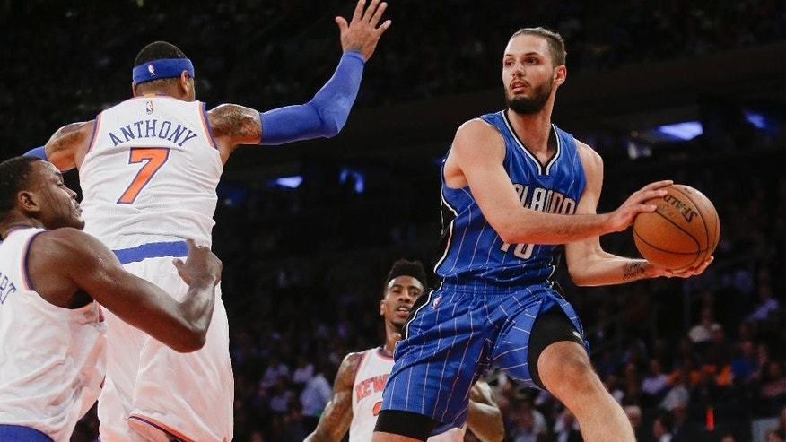 Orlando Magic's Evan Fournier (10) passes the ball away from New York Knicks' Carmelo Anthony (7) and Samuel Dalembert during the first half of an NBA basketball game Wednesday, Nov. 12, 2014, in New York.  (AP Photo/Frank Franklin II)