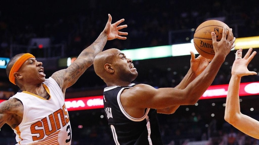 Brooklyn Nets' Jarrett Jack (0) drives past Phoenix Suns' Isaiah Thomas (3) during the first half of an NBA basketball game Wednesday, Nov. 12, 2014, in Phoenix. (AP Photo/Ross D. Franklin)