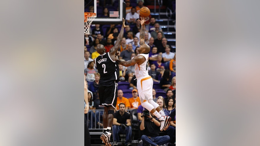 Phoenix Suns' P.J. Tucker, right, gets a shot off over Brooklyn Nets' Kevin Garnett (2) during the first half of an NBA basketball game Wednesday, Nov. 12, 2014, in Phoenix. (AP Photo/Ross D. Franklin)