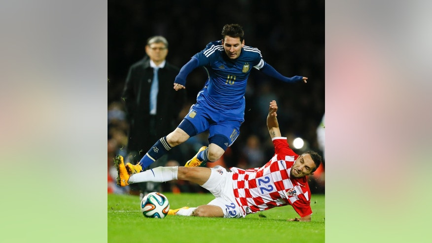 Argentina's Lionel Messi  vies for the ball with Croatia's Marin Leovac during the international friendly soccer match between Argentina and Croatia at the Boleyn Ground in London, Wednesday, Nov. 12, 2014. (AP Photo/Kirsty Wigglesworth)