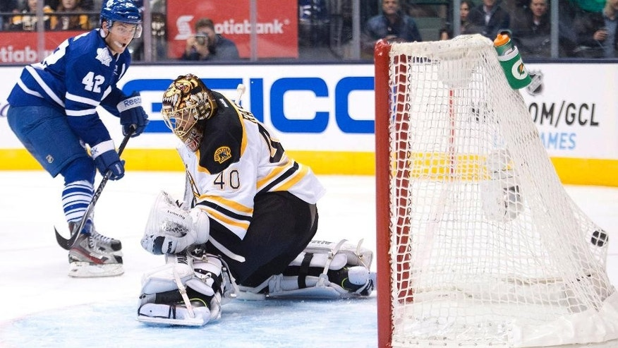 Toronto Maple Leafs forward Tyler Bozak, left, scores past Boston Bruins goalie Tuukka Rask during the second period of an NHL hockey game Wednesday, Nov. 12, 2014, in Toronto. (AP Photo/The Canadian Press, Nathan Denette)