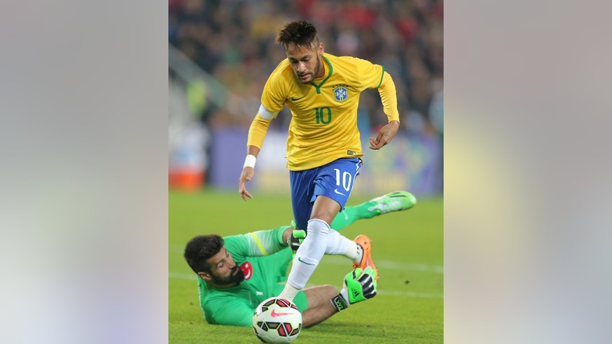Brazil's Neymar JR, top, passes Turkey's goalkeeper Volkan Demirel during their friendly soccer match at Sukru Saracoglu Stadium in Istanbul, Turkey, Wednesday, Nov. 12, 2014. (AP Photo)