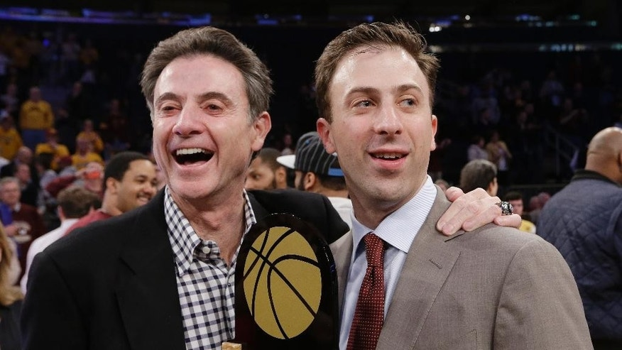 FILE - This April 3, 2014, file photo shows Minnesota coach Richard Pitino, right, standing with his father, Rick Pitino, after Minnesota's 65-63 win over SMU in an NCAA college basketball game in the final of the NIT  in New York. No. 8 Louisville and Minnesota have a mutual goal of starting the season Friday, Nov. 14, 2014, in Puerto Rico with a quality win, but it's not that simple considering the opposing coaches respectively are the Cardinals' Rick Pitino and his son Richard, the Gophers' second-year head man and former U of L assistant. (AP Photo/Frank Franklin II, File)