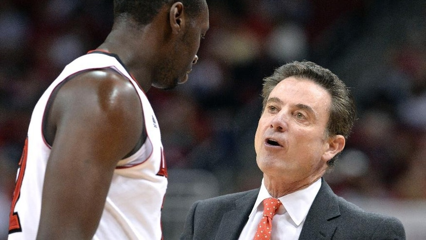 Louisville head coach Rick Pitino, right, talks with Akoy Agau during the second half of their NCAA college basketball game against Bellarmine, Sunday Nov. 9, 2014, in Louisville, Ky. (AP Photo/Timothy D. Easley)
