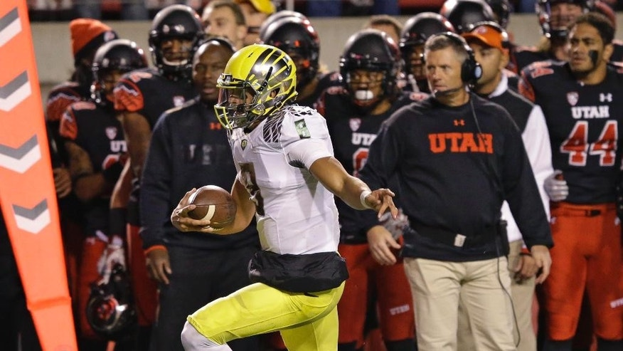 Utah defensive back Marcus Williams (20) tackles Oregon quarterback Marcus Mariota (8) as stretches to make a first down in the first quarter during an NCAA college football game Saturday, Nov. 8, 2014, in Salt Lake City. (AP Photo/Rick Bowmer)
