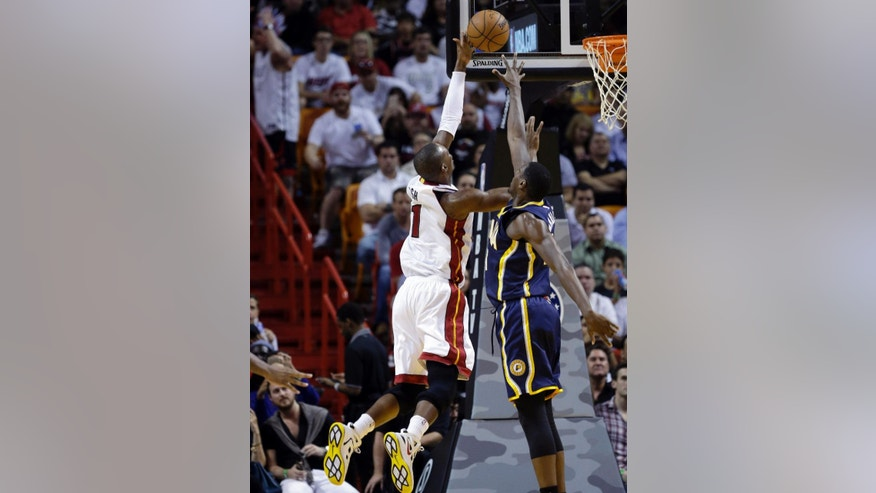 Miami Heat's Chris Bosh (1) shoots over Indiana Pacers' Donald Sloan, right, in the first half of an NBA basketball game, Wednesday, Nov. 12, 2014, in Miami. (AP Photo/Lynne Sladky)