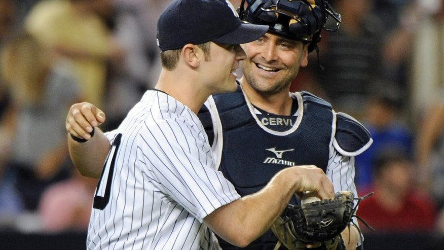 FILE - In this July 25, 2014, file photo, New York Yankees closer David Robertson, left, celebrates with catcher Francisco Cervelli after the Yankees defeated the Toronto Blue Jays in a baseball game at Yankee Stadium in New York. The Pittsburgh Pirates have acquired catcher Cervelli from the New York Yankees in exchange for reliever Justin Wilson. (AP Photo/Bill Kostroun, File)