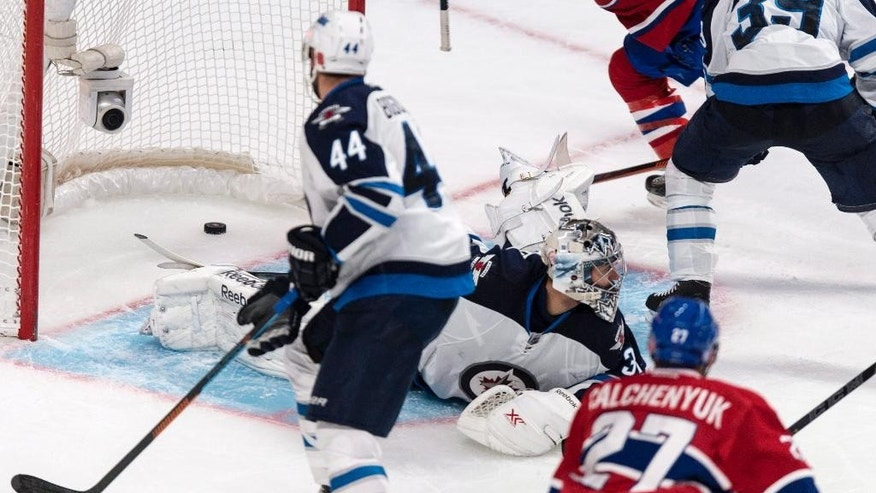 Montreal Canadiens' Alex Galchenyuk scores past Winnipeg Jets goalie Ondrej Pavelec as Jets' Zach Bogosian watches during the third period of an NHL hockey game Tuesday, Nov. 11, 2014, in Montreal. The Canadiens won 3-0. (AP Photo/The Canadian Press, Paul Chiasson)