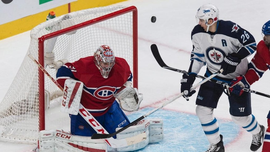 Montreal Canadiens goalie Carey Price loses sight of the puck as Winnipeg Jets' Blake Wheeler tries for the rebound during the second period of an NHL hockey game Tuesday, Nov. 11, 2014, in Montreal. (AP Photo/The Canadian Press, Paul Chiasson)