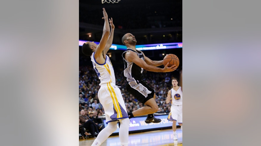 San Antonio Spurs' Tony Parker, right, looks to shoot against Golden State Warriors' Shaun Livingston during the first half of an NBA basketball game Tuesday, Nov. 11, 2014, in Oakland, Calif. (AP Photo/Marcio Jose Sanchez)
