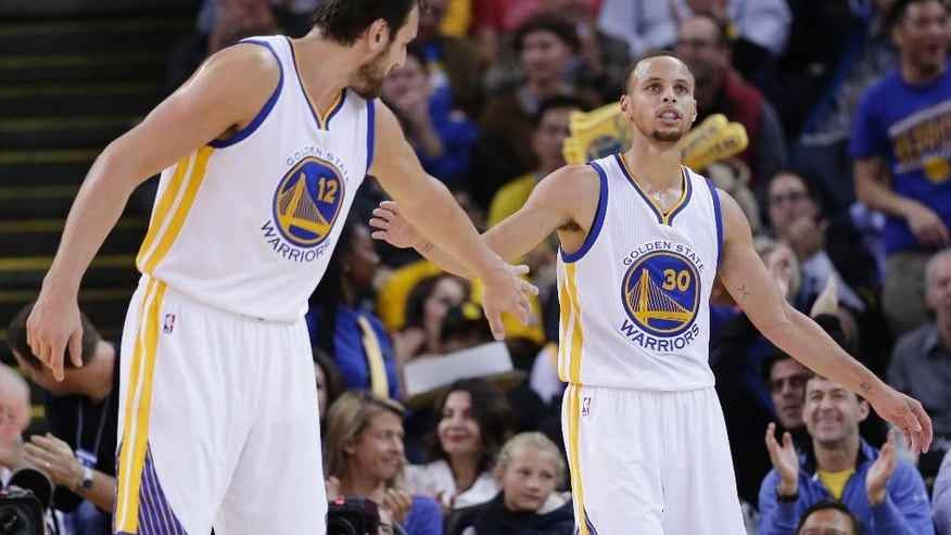 Golden State Warriors' Stephen Curry (30) slaps hands with Andrew Bogut after Curry scored against the San Antonio Spurs during the first half of an NBA basketball game Tuesday, Nov. 11, 2014, in Oakland, Calif. (AP Photo/Marcio Jose Sanchez)