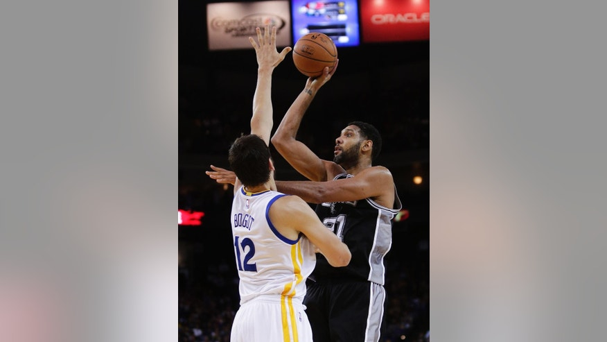 San Antonio Spurs' Tim Duncan shoots over Golden State Warriors' Andrew Bogut during the first half of an NBA basketball game Tuesday, Nov. 11, 2014, in Oakland, Calif. (AP Photo/Marcio Jose Sanchez)