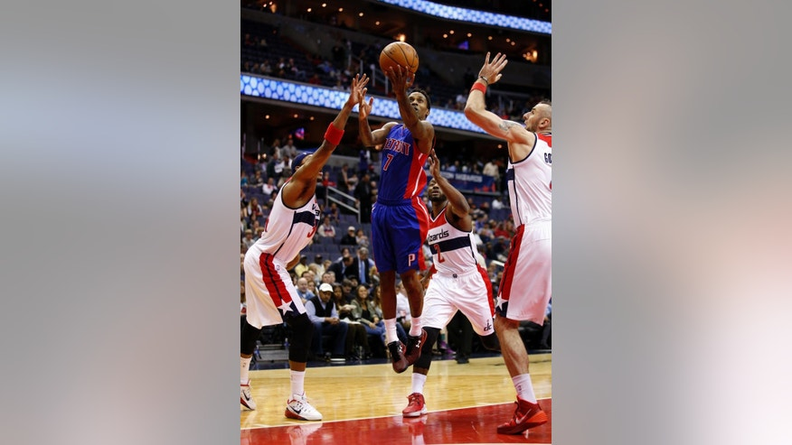 Detroit Pistons guard Brandon Jennings (7) shoots between Washington Wizards forward Paul Pierce (34), guard John Wall (2) and center Marcin Gortat, right, from Poland, in the first half of an NBA basketball game, Wednesday, Nov. 12, 2014, in Washington. (AP Photo/Alex Brandon)