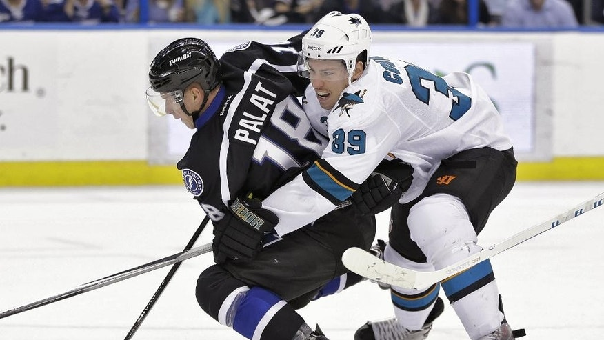 San Jose Sharks center Logan Couture (39) drags down Tampa Bay Lightning left wing Ondrej Palat (18), of the Czech Republic, during the second period of an NHL hockey game Thursday, Nov. 13, 2014, in Tampa, Fla. (AP Photo/Chris O'Meara)